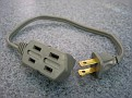 Small USA extension cord to be able to plug in multiple items in case there is only one receptacle.  The two brass prongs / blades will fit into any Plug Adaptor mentioned here.  You can do the same with your own Country Plug Adaptors and your own cord.